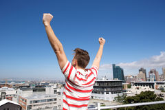 Behind of young man with arms raised outsice Stock Image