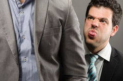 Behind your back. Image of a male professional making faces behind someone's back Royalty Free Stock Images