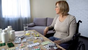 Behinderte ältere Dame im Rollstuhl, der die Medizin, bleibend im Pflegeheim einnimmt stockfotografie
