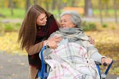 Behinderte ältere Frau und junge Pflegekraft stockfotografie