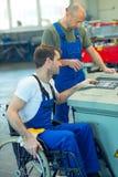 Behinderte Arbeitskraft im Rollstuhl in der Fabrik und im Kollegen Stockbild