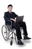 Behinderte Arbeitskraft mit Laptop auf Rollstuhl Lizenzfreie Stockbilder