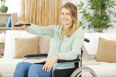 Behinderte Frau in aufpassenden Filmen des Rollstuhls zu Hause stockbild