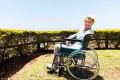 Behinderte Frau, die draußen sitzt Lizenzfreie Stockbilder