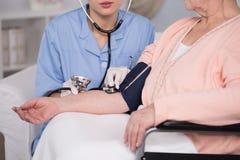 Behinderte Frau, die Druck gemessen wird Stockbilder