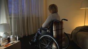 Behinderte Frau im Rollstuhl, der durch das Fenster auf Straße, Einsamkeit schaut stock video footage