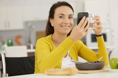 Behinderte Frau unter Verwendung des Telefons und des Haltens des Glaswassers lizenzfreies stockfoto