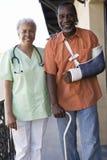 Behinderte geduldige Stellung mit Doktor lizenzfreies stockfoto