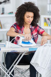 Behinderte junge Frau, die im Wohnzimmer bügelt stockfotos