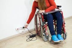 Behinderte kaukasische Frau hat einige Fragen wenn EinsatzNetzstecker Rollstuhlsitzen Stockbilder