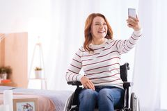 Behinderte lächelnde Frau, die Fotos macht Stockbild