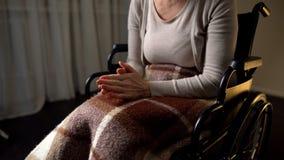 Behinderte nervöse Frau, die Hände, fühlend einsam und, Rollstuhl zusammenpreßt hilflos lizenzfreie stockfotos