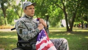 Behinderter amerikanischer Veteran, der Flagge zum Herzen sich erinnert Krieg, Glauben und an Stolz setzt stock footage