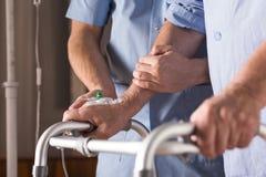 Behinderter, der mit Unterstützung geht stockbild