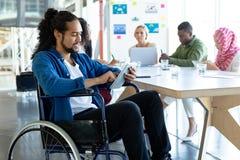 Behinderter Geschäftsmann, der digitale Tablette im Konferenzsaal während des Treffens verwendet lizenzfreie stockfotografie