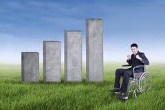 Behinderter Geschäftsmann mit einer Wachstumstabelle draußen Stockfoto