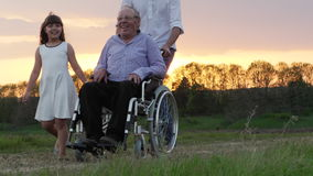 Behinderter Großvater wird in einen Rollstuhl gefahren stock footage