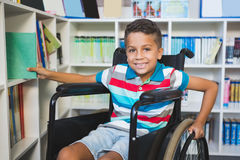 Behinderter Junge, der ein Buch vom Bücherregal in der Bibliothek vorwählt lizenzfreies stockbild
