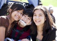 Behinderter Junge im Rollstuhl umgeben von den großen Schwestern, lächelnd Stockbilder