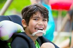 Behinderter Junge mit acht Jährigen beim Rollstuhllächeln Lizenzfreie Stockfotos