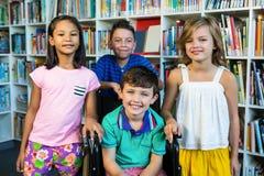 Behinderter Junge mit Freunden an der Bibliothek in der Schule Stockfoto