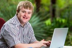 Behinderter junger Mann, der auf Laptop im Garten schreibt lizenzfreies stockfoto