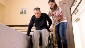 Behinderter junger Mann, der auf Rollstuhl überträgt stock video footage