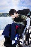 Behinderter kleiner Junge im Rollstuhl heraus auf Pier durch See Stockfotografie