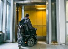 Behinderter Mann auf dem Rollstuhl, der in Aufzug geht lizenzfreies stockbild