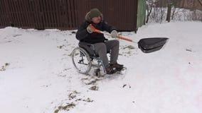 Behinderter Mann auf dem Rollstuhl, der mit Schneeschaufel arbeitet stock footage
