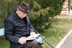 Behinderter Mann auf Krücken lesend im Park Lizenzfreie Stockfotografie
