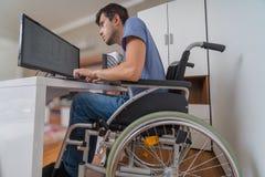 Behinderter behinderter Mann auf Rollstuhl arbeitet mit Computer im Büro Lizenzfreies Stockfoto