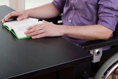 Behinderter Mann, der ein Buch liest Stockbild