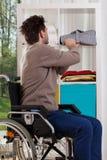 Behinderter Mann, der Hemd auf Regal setzt Lizenzfreie Stockfotografie