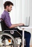 Behinderter Mann, der im Internet surft Stockfoto