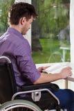 Behinderter Mann, der zu Hause ein Buch liest Stockbild