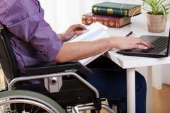 Behinderter Mann, der zu Hause studiert Lizenzfreie Stockfotos