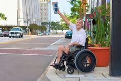 Behinderter Mann in einem Rollstuhl, der eine wellenartig bewegende Zeitung des Taxis hagelt lizenzfreies stockfoto