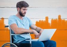 Behinderter Mann im Rollstuhl mit hellem gemaltem orange Hintergrund Lizenzfreie Stockfotografie
