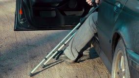 Behinderter Mann mit Krücken im Auto stock video footage
