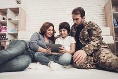 Behinderter Mann-Soldat Watch ein Tablet mit Familie lizenzfreie stockfotografie