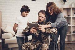 Behinderter Mann-Soldat Watch ein Tablet mit Familie stockfoto