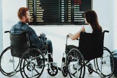 Behinderter Mann und Frau nahe schwarzen Flughafen-Plakaten lizenzfreies stockbild