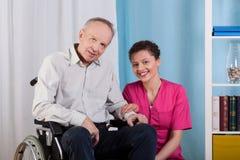Behinderter Mann und Krankenschwester in einem Pflegeheim Stockbild