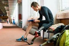 Behinderter Sportler, der auf Bank sitzt lizenzfreie stockfotografie