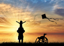 Behindertes Kind auf den Schultern des Vatis spielend mit Drachen und Rollstuhl nahe Seesonnenuntergang Lizenzfreies Stockbild