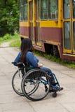 Behindertes Mädchen, das auf eine Tram wartet Stockfotografie