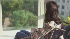 Behindertes Mädchen, das am Fenster in einem Rollstuhl sitzt Langsames MO stock footage