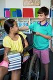 Behindertes Mädchen, das Jungen in der Bibliothek betrachtet Lizenzfreies Stockfoto