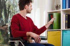 Behindertes Mann cleanig herauf ein Bücherregal stockfotografie